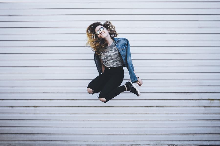 女性が笑顔でジャンプしている写真
