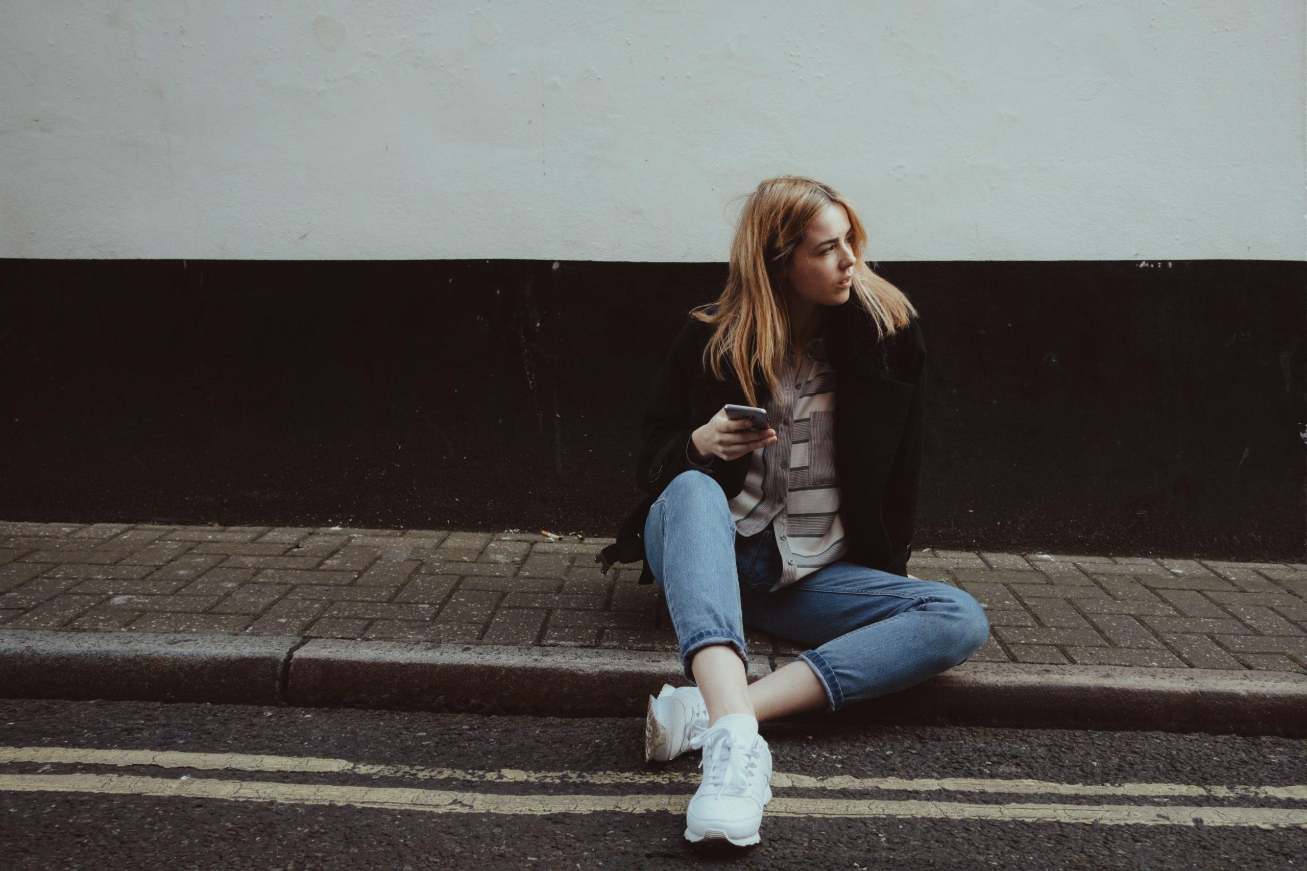 スマホを持って座っている女性の画像